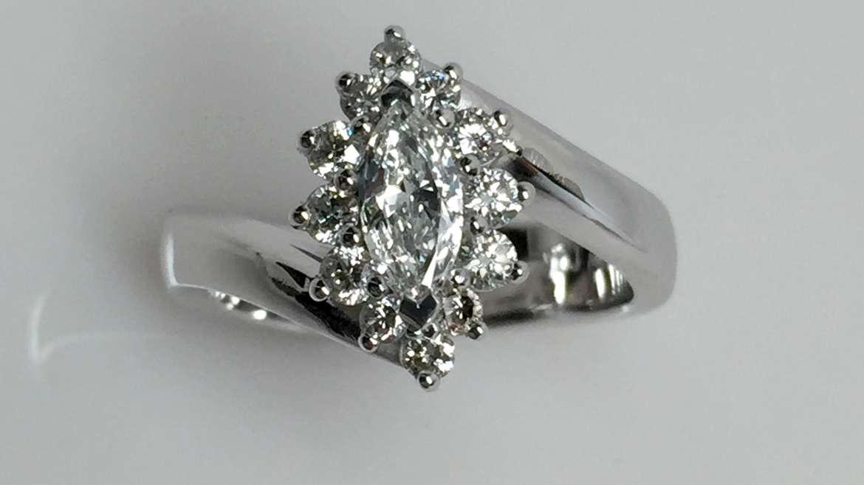 Bague or blanc serti d'un diamant de taille marquise de 0.32ct et 12 diamants ronds pour un total de 0.35 ct